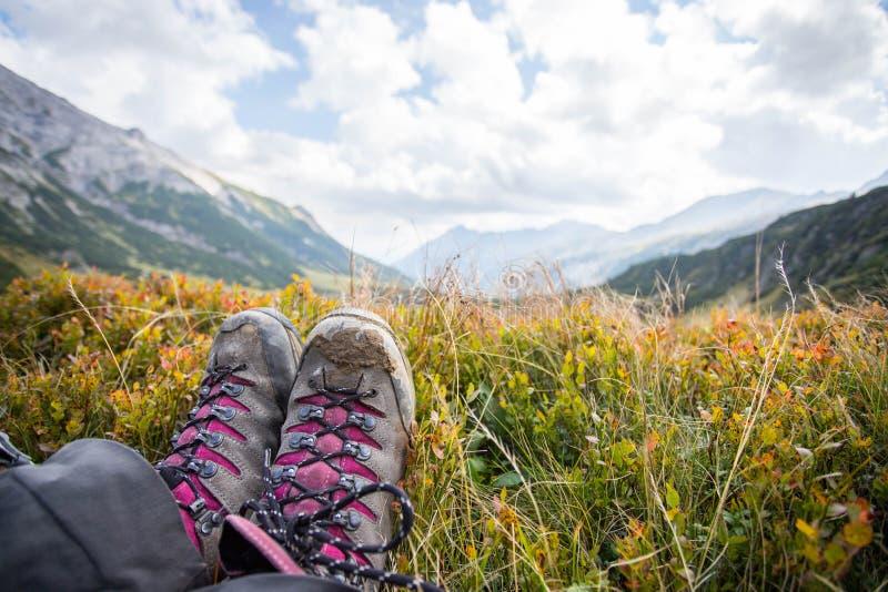 Botas alpinas en el primero plano, paisaje id?lico de la monta?a en el fondo borroso imagen de archivo