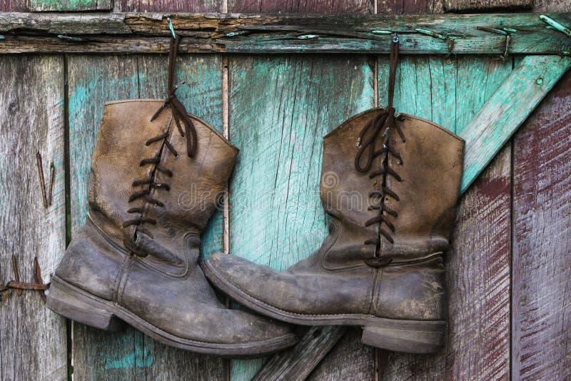 Botas americanas de trabalho velhas no fundo da madeira do vintage fotos de stock