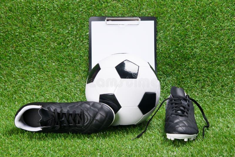 Botas, bola do futebol e tabuleta para escrever, na perspectiva da grama fotografia de stock