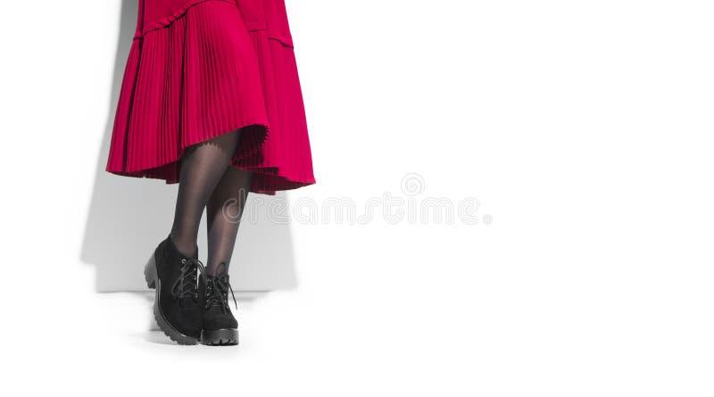 Botas da forma da mulher, calçados elegantes Pés da jovem mulher em sapatas pretas da camurça Midi vermelho plissou a saia fotografia de stock royalty free