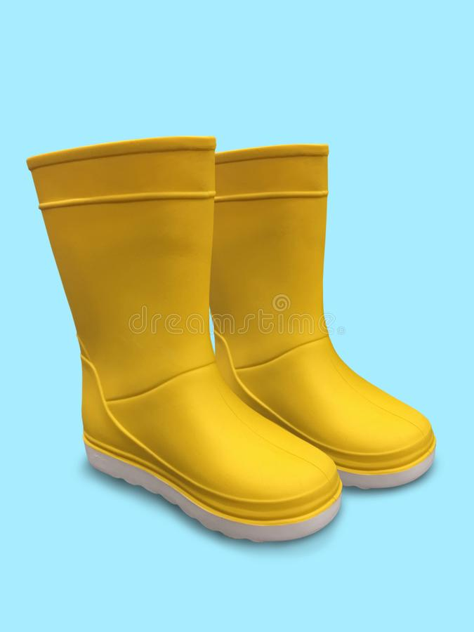 Botas de borracha amarelas no fundo azul Sola branca imagem de stock