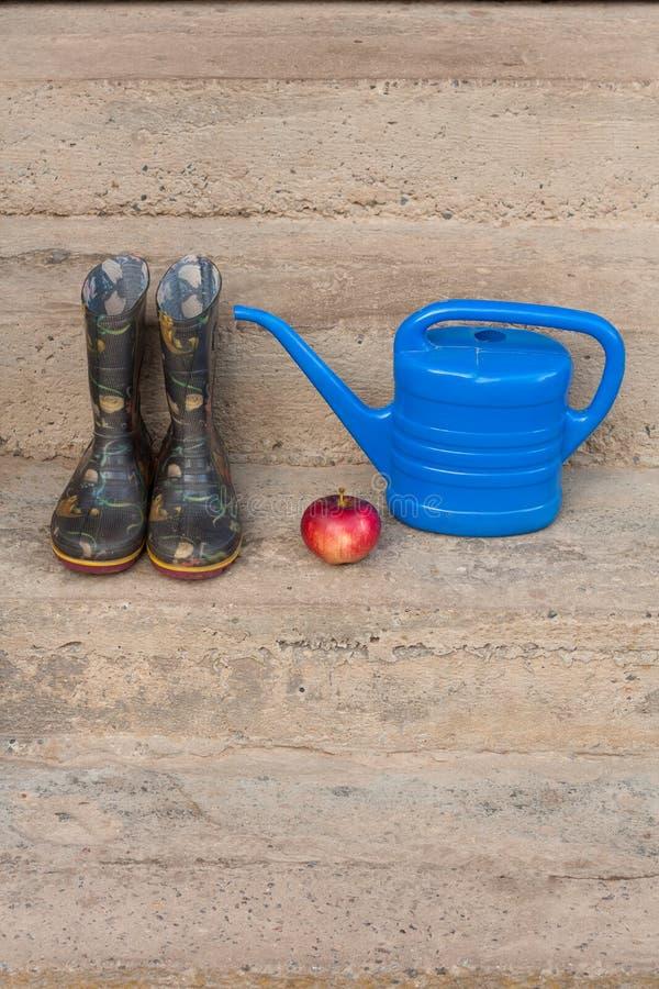 Botas de borracha, Apple vermelho e lata molhando azul pequena fotos de stock