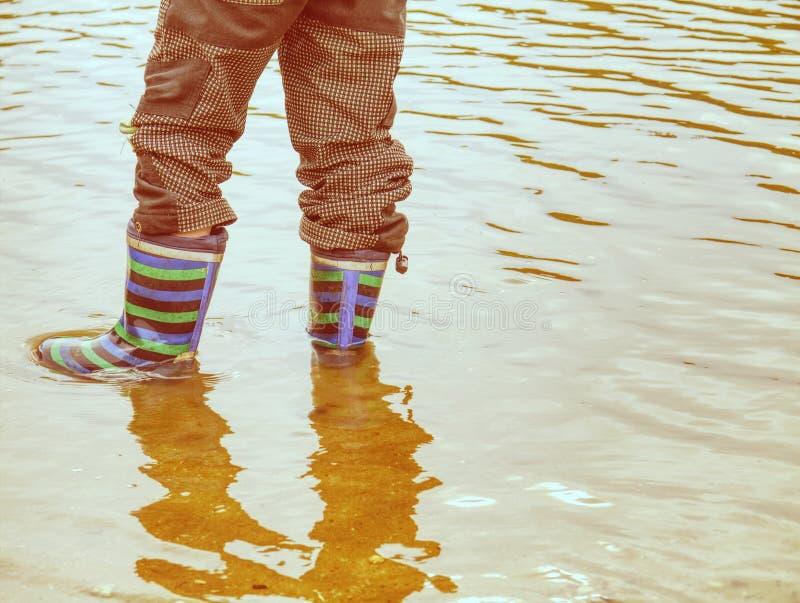 Botas de borracha na poça enlameada da água, nível de água ondulado fotografia de stock