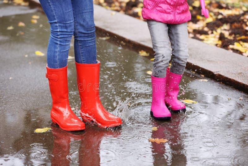 Botas de borracha vestindo da mãe e da filha que espirram na poça no dia chuvoso, foco dos pés foto de stock
