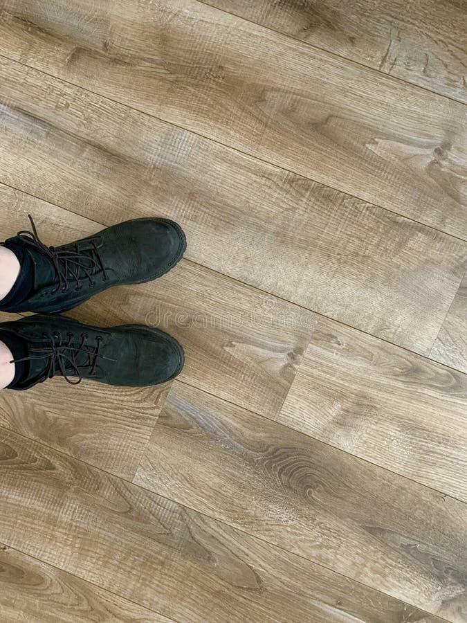 Botas de caminhada de couro pretas em um assoalho de madeira fotografia de stock