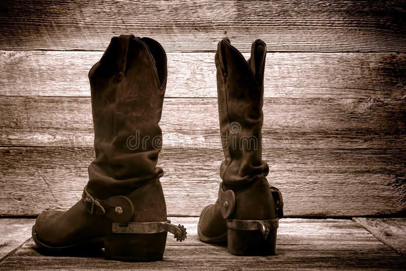 Botas de cowboy ocidentais americanas do rodeio no celeiro de madeira velho fotografia de stock