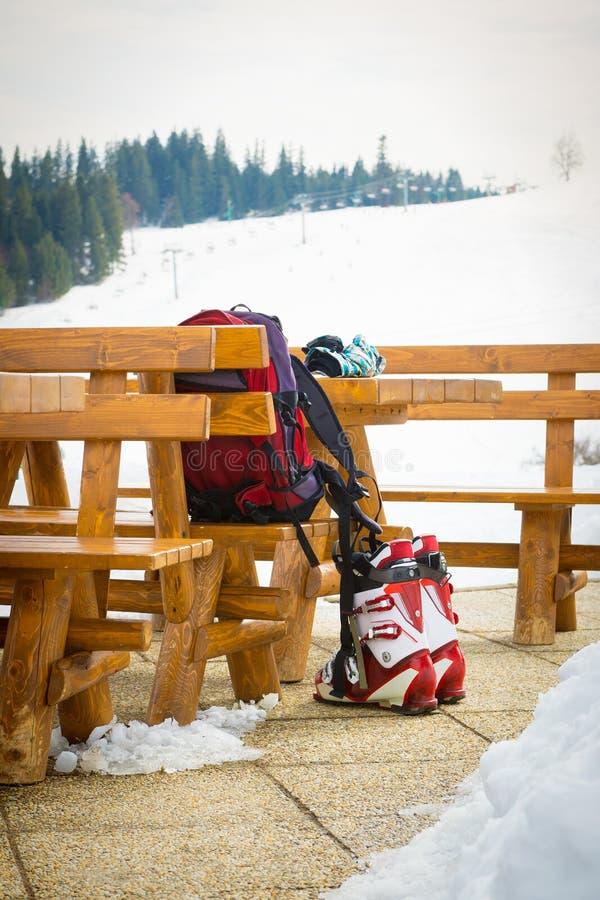 Botas de esqui, luvas e uma trouxa em uma barra exterior em uma estância de esqui fotos de stock royalty free