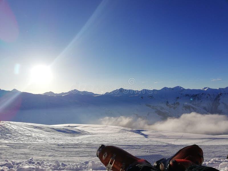 Botas de esqui que relaxam no Mountain View nevado ensolarado imagem de stock