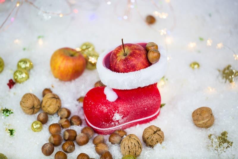 Botas de Santa Claus con las nueces, mandarinas, manzanas, en la nieve fotos de archivo