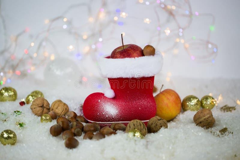 Botas de Santa Claus con las nueces, mandarinas, manzanas, en la nieve imagen de archivo
