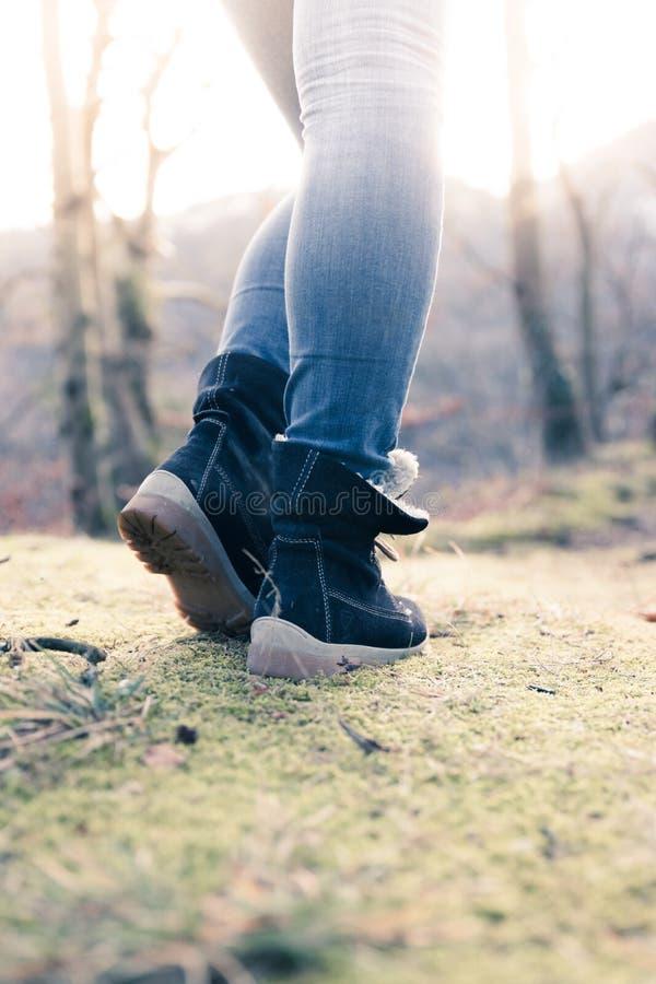 Botas de una mujer joven, recorte, aire libre en tierra de bosques maderables, otoño fotografía de archivo