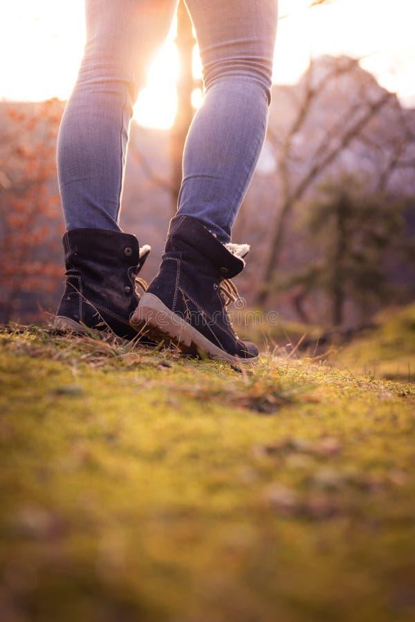 Botas de una mujer joven, recorte, aire libre en tierra de bosques maderables, otoño imagenes de archivo