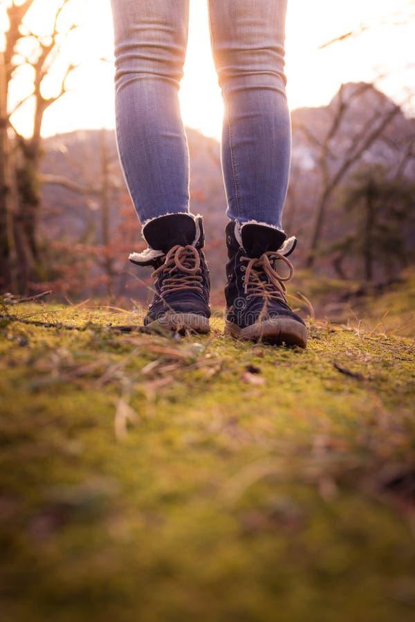 Botas de una mujer joven, recorte, aire libre en tierra de bosques maderables, otoño foto de archivo