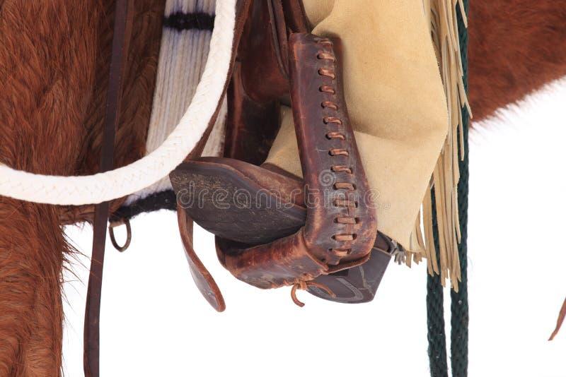 Botas de vaqueiro nos estribos fotografia de stock royalty free