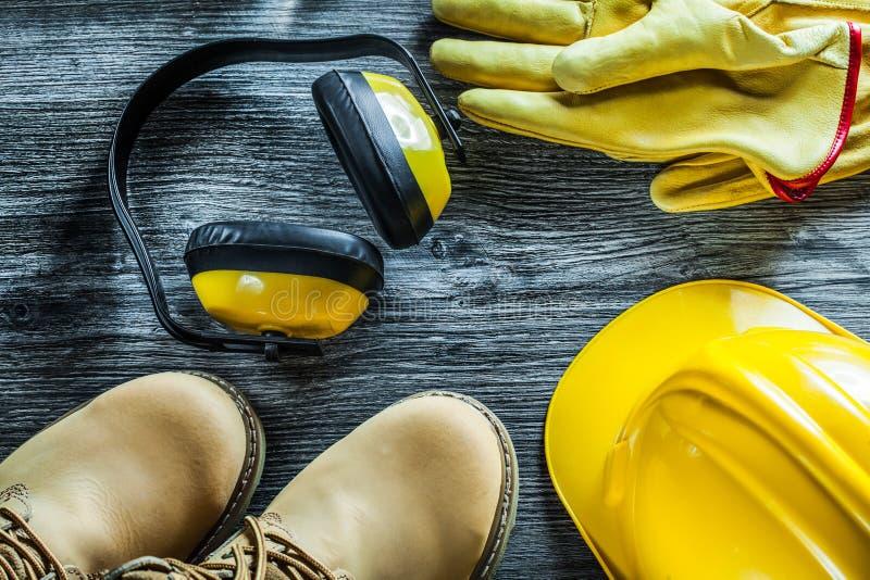 Botas del casquillo de seguridad de los guantes protectores de las orejeras en el tablero de madera imágenes de archivo libres de regalías