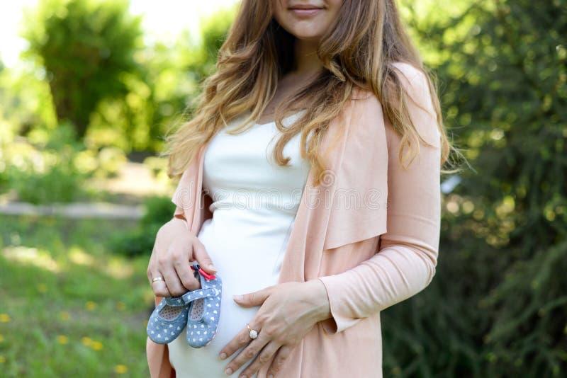Botas do bebê da terra arrendada da mulher gravida fora no fundo da natureza da mola fotos de stock
