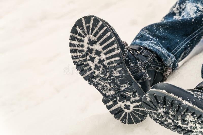 Botas do inverno nos p?s de um menino que encontra-se na neve imagem de stock royalty free