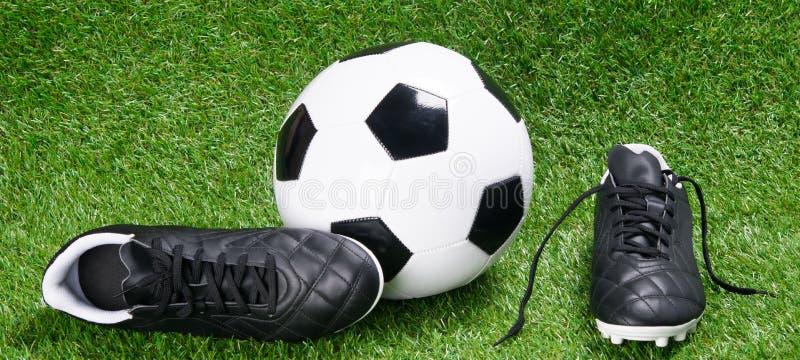 Botas e bola do futebol para o futebol, na perspectiva da grama fotos de stock royalty free