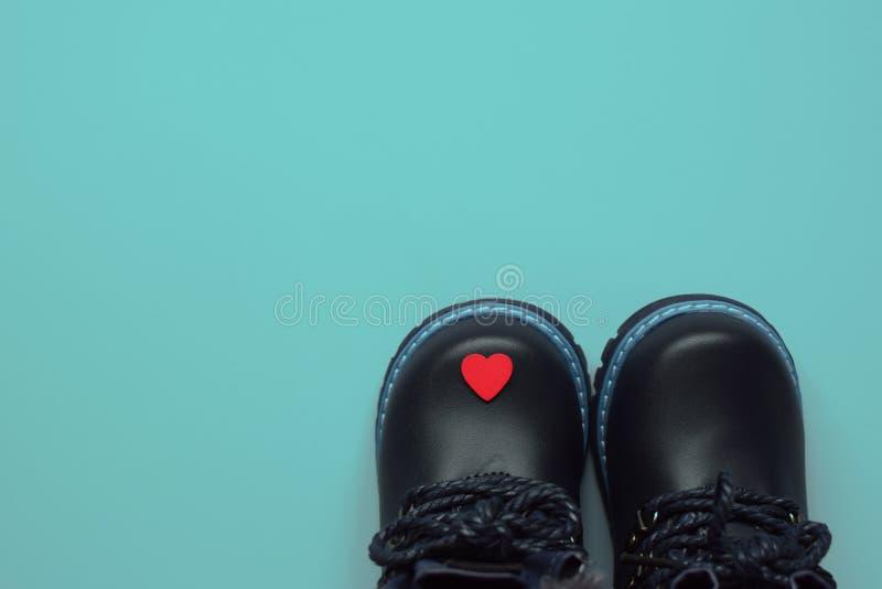 Botas e coração pretos do inverno do ` s da criança foto de stock