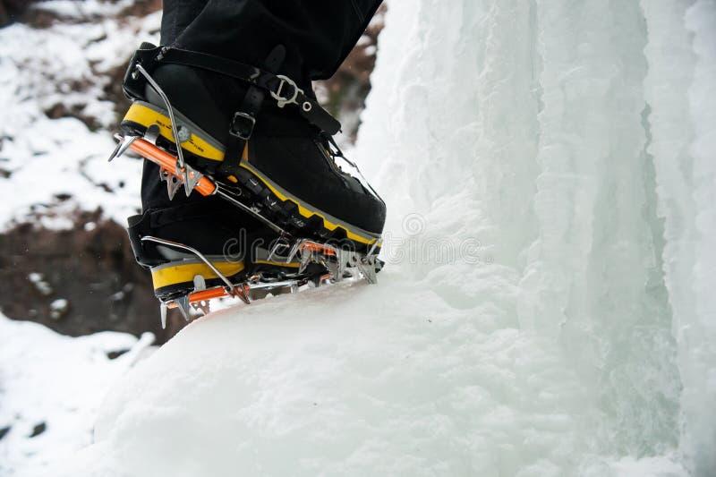 Botas e ganchos de ferro de um montanhista de gelo em uma cachoeira congelada foto de stock