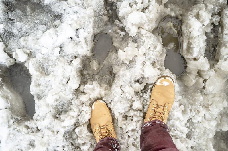 Botas e lama amarelas em uma estrada nevado como um obstáculo à passagem dos pedestres fotos de stock royalty free