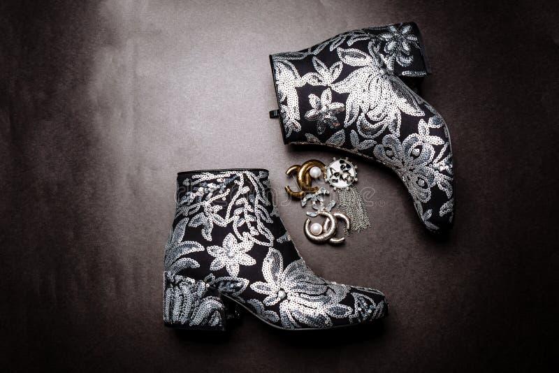 Botas grosso-colocadas saltos pretas do tornozelo decoradas com as flores bordadas com lantejoulas e os broches de prata em um fu fotografia de stock