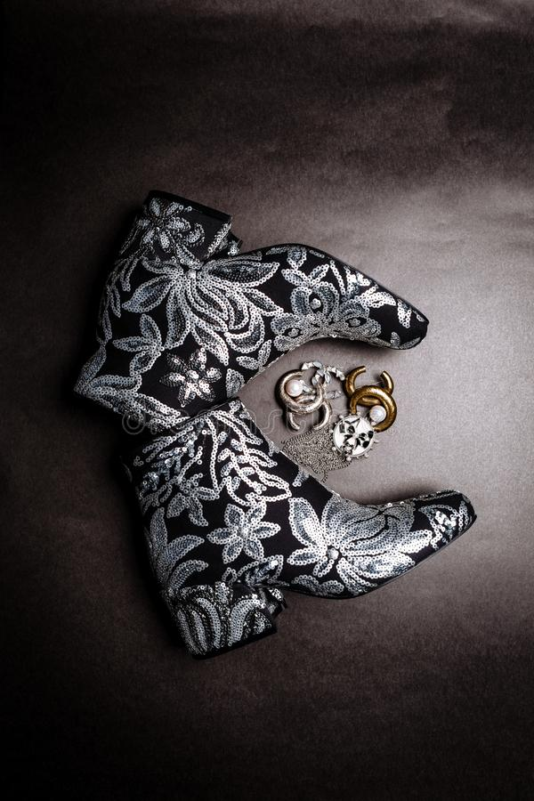Botas grosso-colocadas saltos pretas do tornozelo decoradas com as flores bordadas com lantejoulas e os broches de prata em um fu foto de stock