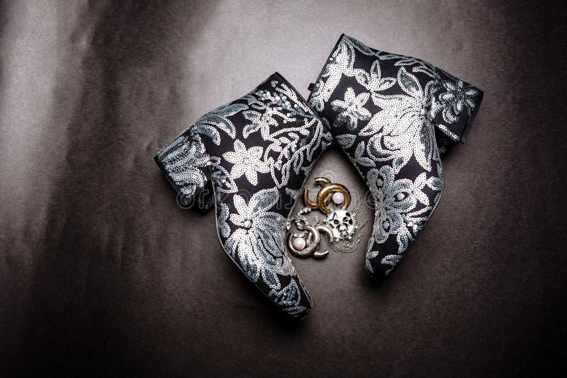 Botas grosso-colocadas saltos pretas do tornozelo decoradas com as flores bordadas com lantejoulas e os broches de prata em um fu imagem de stock royalty free