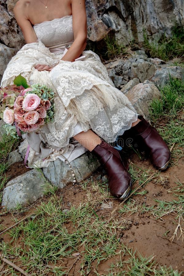 Botas marrones elegantes de las novias occidentales que sostienen un ramo elegante de la flor El sentarse en un paso en un vestid imagenes de archivo