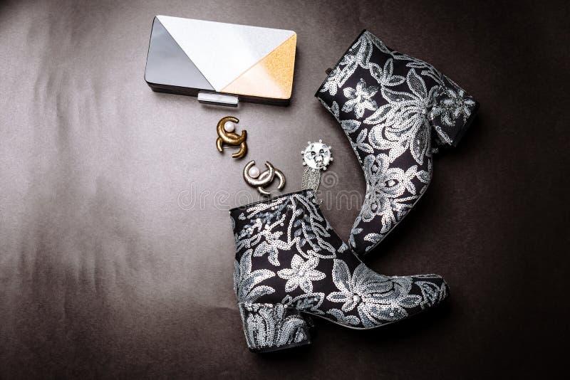 Botas pretas do tornozelo com os saltos grossos decorados com as flores bordadas com lantejoulas de prata e uma embreagem e broch imagens de stock royalty free