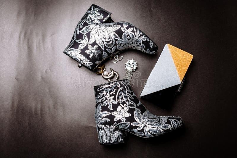Botas pretas do tornozelo com os saltos grossos decorados com as flores bordadas com lantejoulas de prata e uma embreagem e broch fotografia de stock royalty free