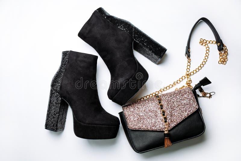 Botas pretas do tornozelo da camur?a em uma plataforma e em uns saltos grossos com sparkles e um saco preto com sparkles na aleta fotografia de stock