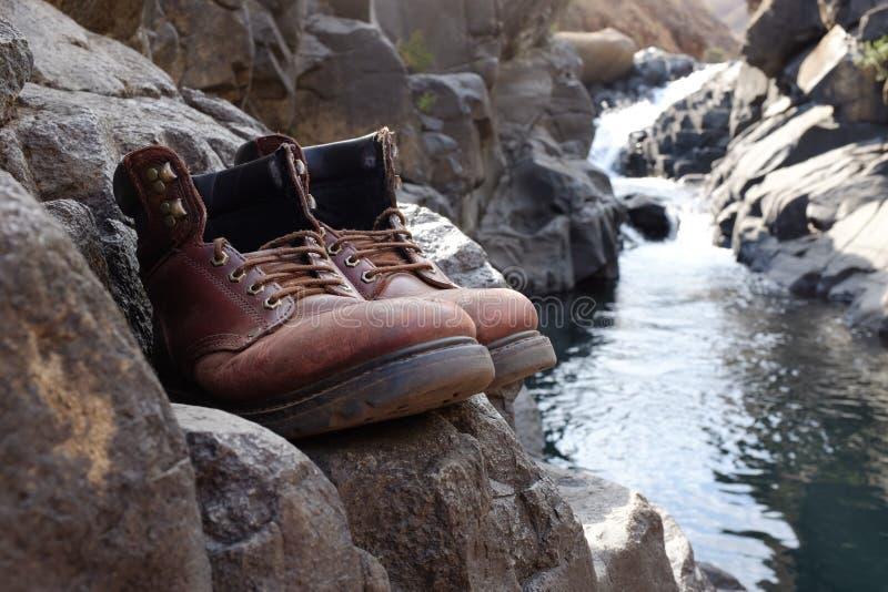Botas que caminan viejas delante de la cascada imagenes de archivo