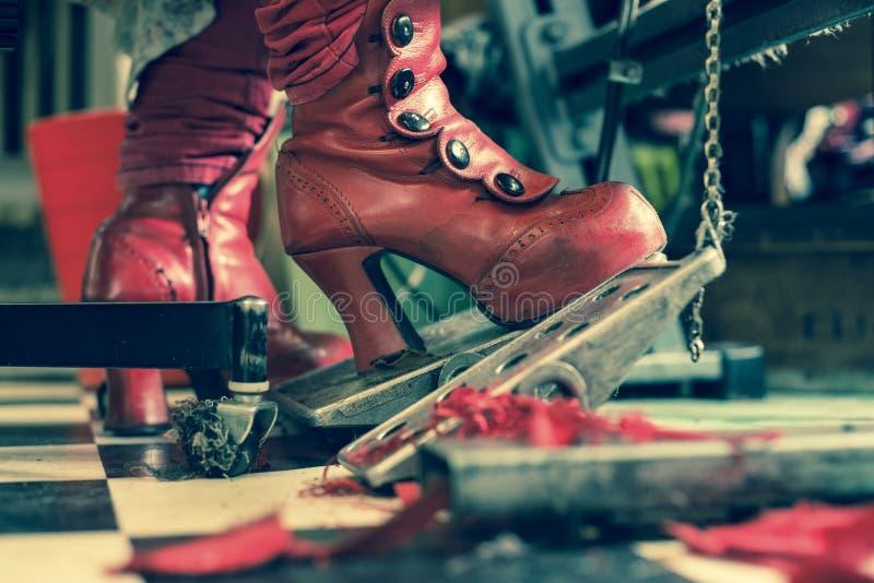Botas rojas de la moda de la costurera en la máquina de coser foto de archivo