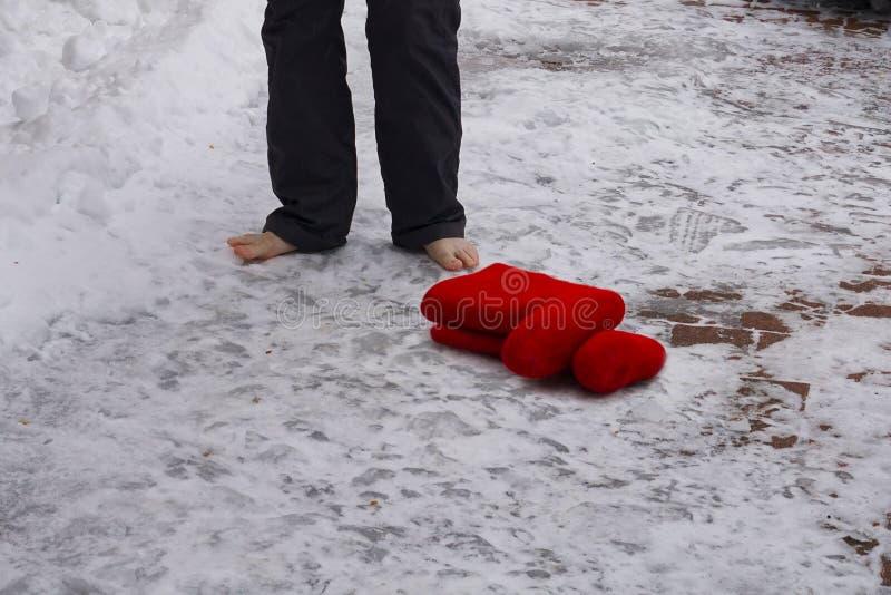 Botas sentidas vermelhas para esperar quando sua senhora andar com os pés descalços na neve fotografia de stock royalty free