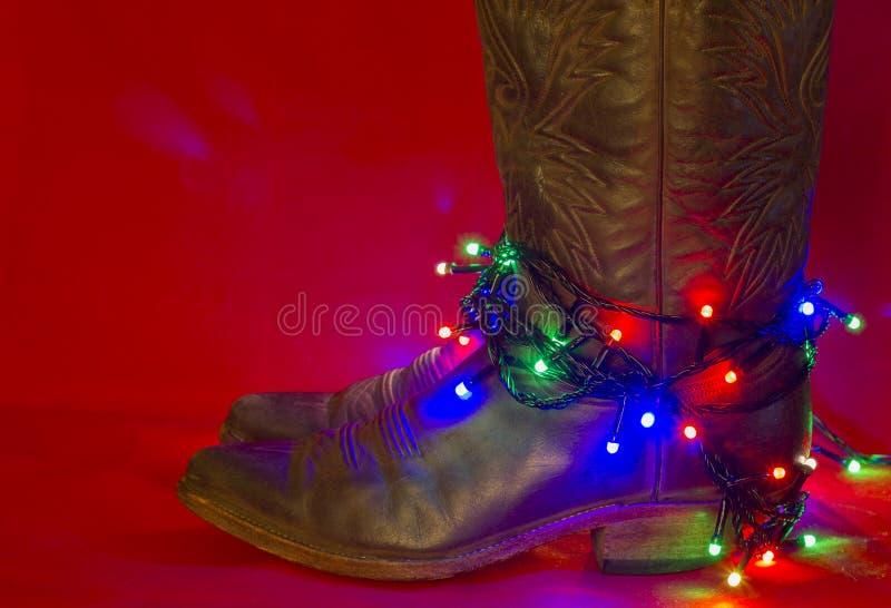 Botas tradicionais ocidentais americanas no fundo vermelho do Natal para fotos de stock