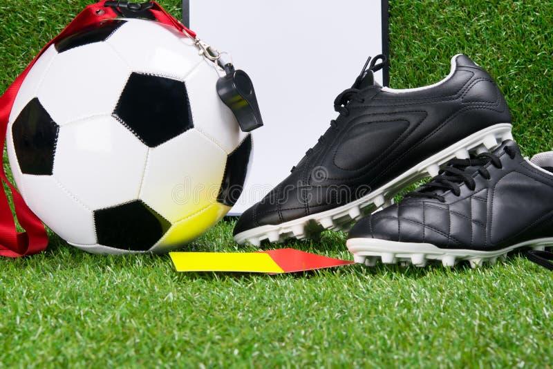 Botas, uma bola do futebol, uma almofada de escrita, um assobio e cartões da pena para um juiz, na perspectiva da grama imagens de stock