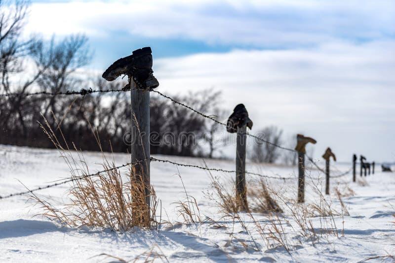 Botas velhas sobre uma cerca Line na neve imagens de stock royalty free