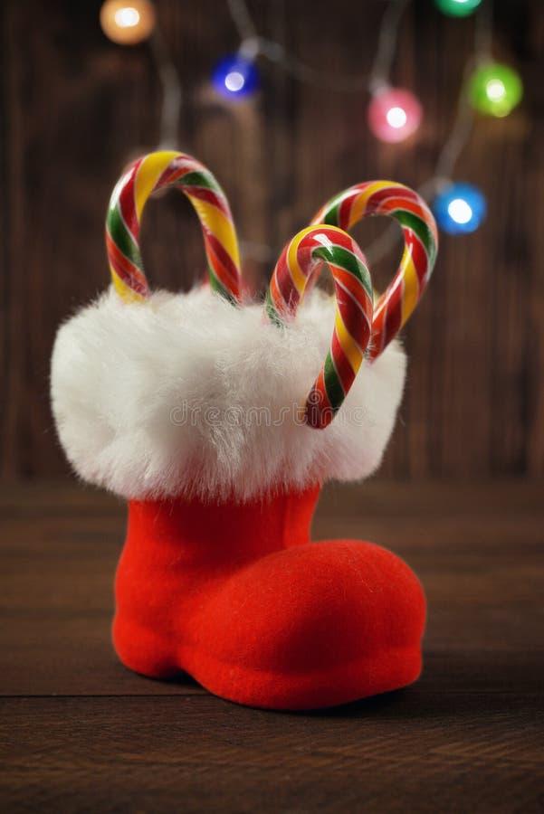 Botas vermelhas do ` s de Santa com o bastão de doces do Natal fotografia de stock