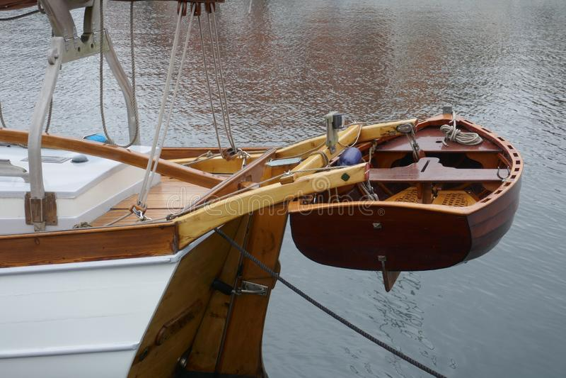 Bote, barco de enfileiramento pequeno feito da madeira de mogno, unido à proa de um iate de navigação fotos de stock royalty free
