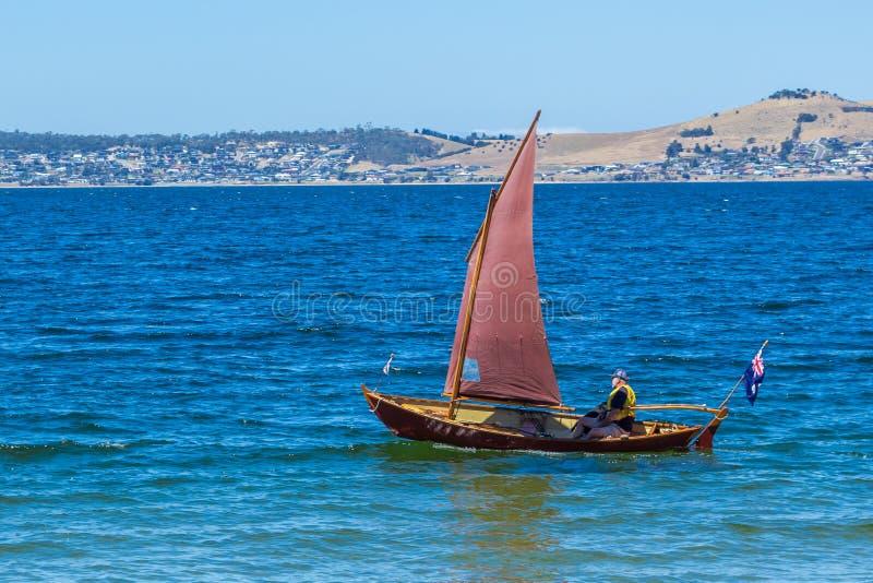 Bote clássico da navigação do clinquer com a vela vermelha na água azul fora da praia arenosa da baía imagens de stock