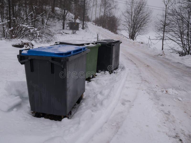 Bote de basura hacia fuera en la nieve del invierno imagen de archivo