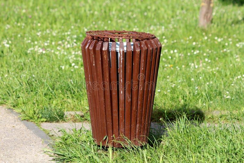 Bote de basura p?blico viejo dilapidado hecho de tableros de madera y del casquillo verticales estrechos del metal al lado de la  fotografía de archivo libre de regalías