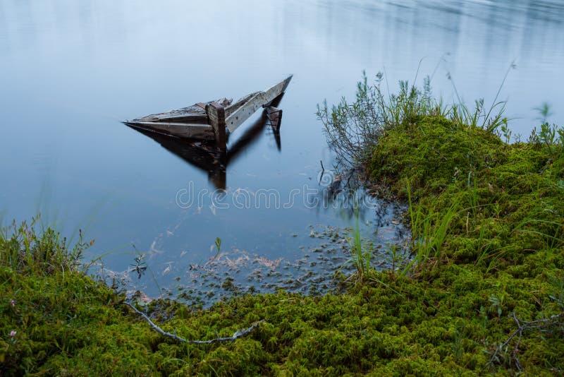 Bote de remos hundido abandonado en el pequeño lago del bosque imagen de archivo