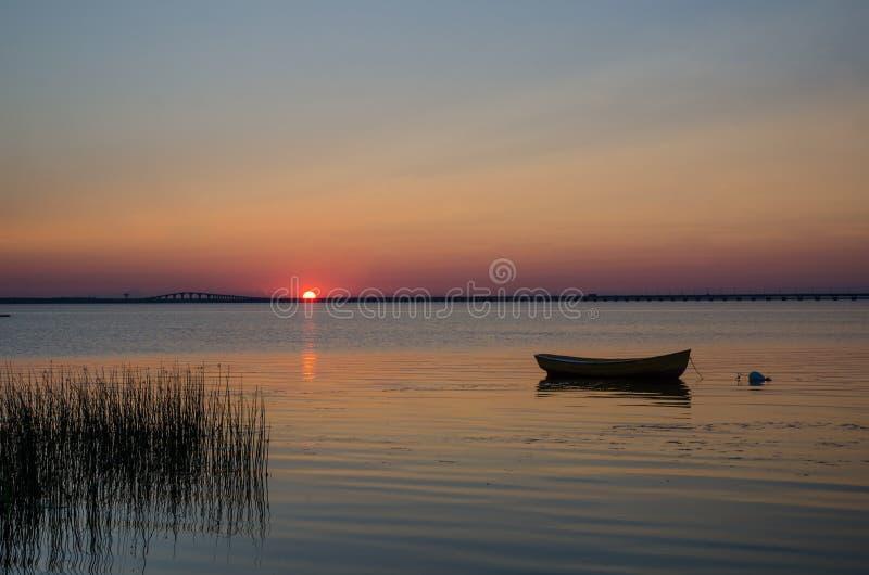 Bote de remos solitario en agua tranquila en la puesta del sol imagen de archivo