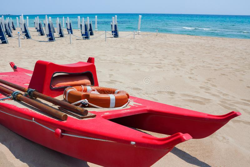 Bote de salvamento com o boia salva-vidas na costa contra da praia e o mar imagens de stock