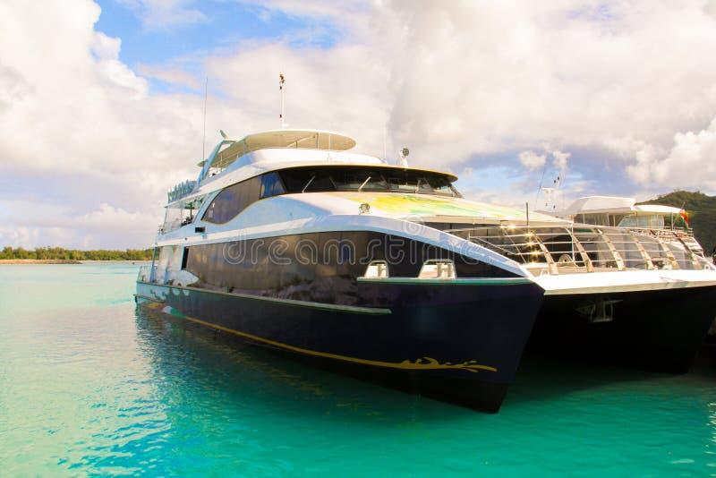 Bote e cruzador fora da costa em tropical fotografia de stock