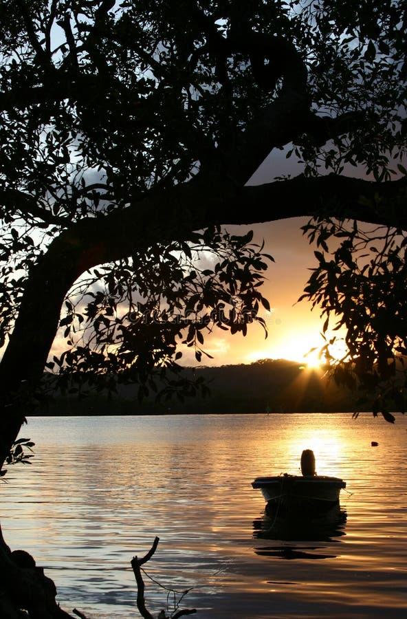 Bote en el agua en la salida del sol fotos de archivo