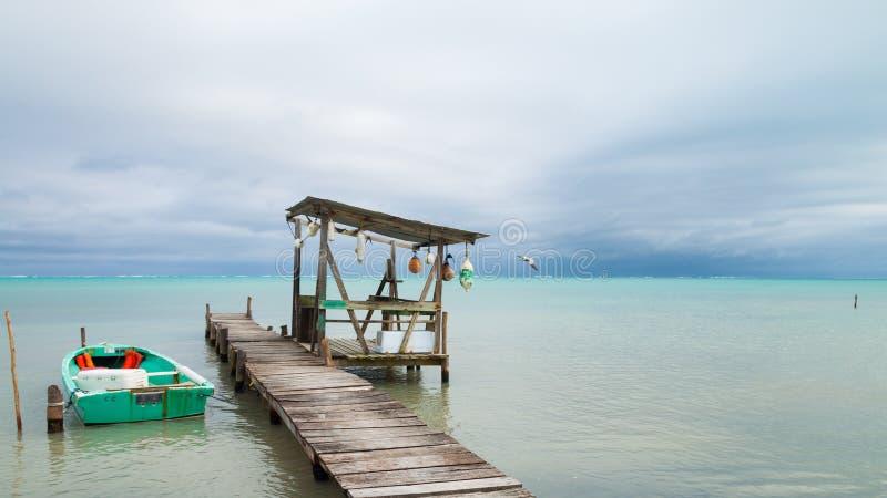Bote pequeño, amarrando los posts, las boyas y el mar tropical cubierto fotografía de archivo libre de regalías