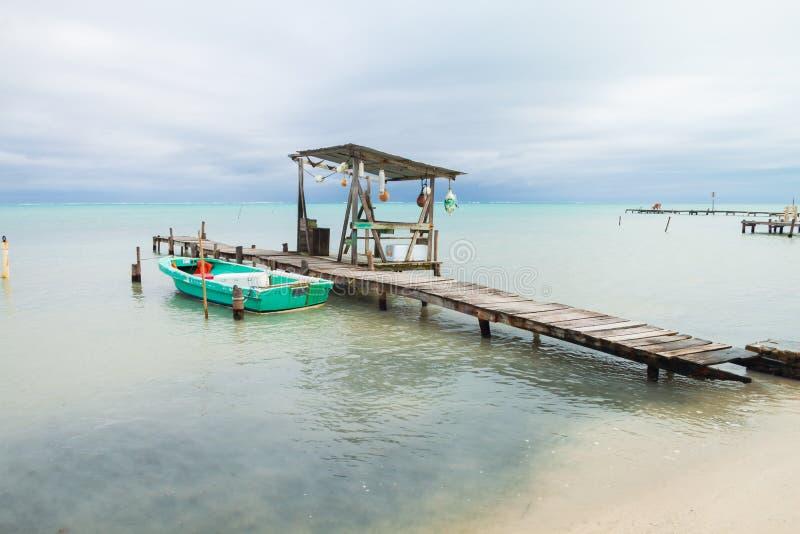 Bote pequeño, amarrando los posts, las boyas y el mar tropical cubierto imagen de archivo libre de regalías